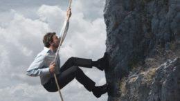 business man climbing mountain